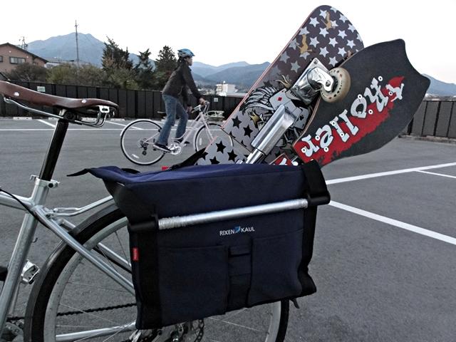 自転車でキャスターボードを運ぶ